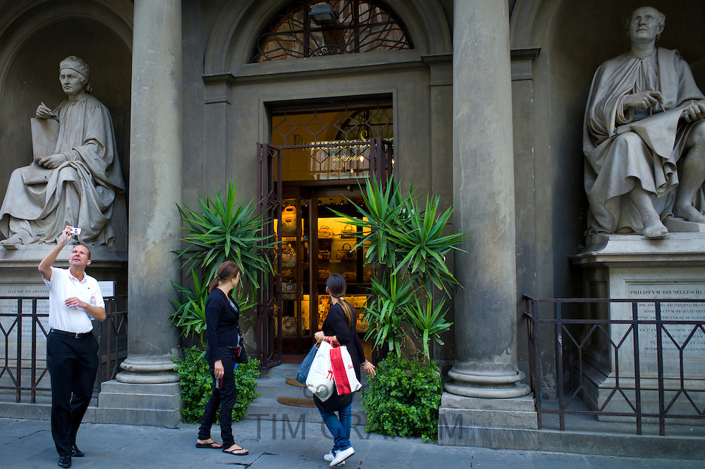 Shoppers by leather goods shop, Florence's Secret, statues of Filipo Brunelleschi, Philippum Brunelleschi Filium in Piazza di San Giovanni, Italy