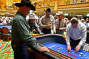 10 DECEMBER 2002 - LAS VEGAS, NEVADA, USA: Cowboys play craps at the Gold Coast Casino in Las Vegas, NV, Dec. 10, 2002 during the National Finals Rodeo. The Gold Coast hosts several cowboy and western themed events, including trophy presentations and dances, during the NFR. The casino is packed every night with cowboys who go to the rodeo or watch live feeds of the rodeo in the casino's bars and then step out of the bar to gamble. PHOTO BY JACK KURTZ