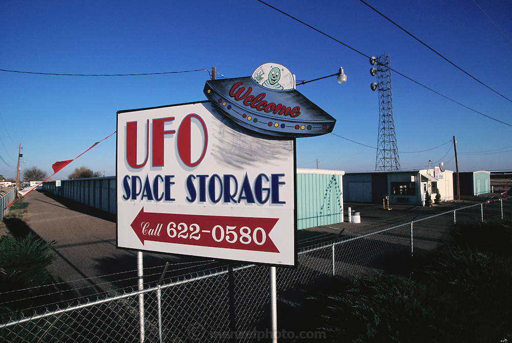 UFO billboard. Sign advertising UFO Space Storage in Roswell, New Mexico, USA. The town has many tourist attractions around the theme of UFO's. It was near Roswell on the evening of 2 July 1947 that many UFO sightings were reported during a thunderstorm. Next morning a rancher, Mac Brazel, discovered strange wreckage in a field. When the impact site was located, a UFO craft and alien bodies were allegedly found. On 8 July 1947, the Roswell Daily Record announced the capture of a flying saucer. The official explanation was that it was a crashed weather balloon. Many Roswell inhabitants, however, believe this a cover up, and Roswell has become a symbol for UFO enthusiasts. (1997).