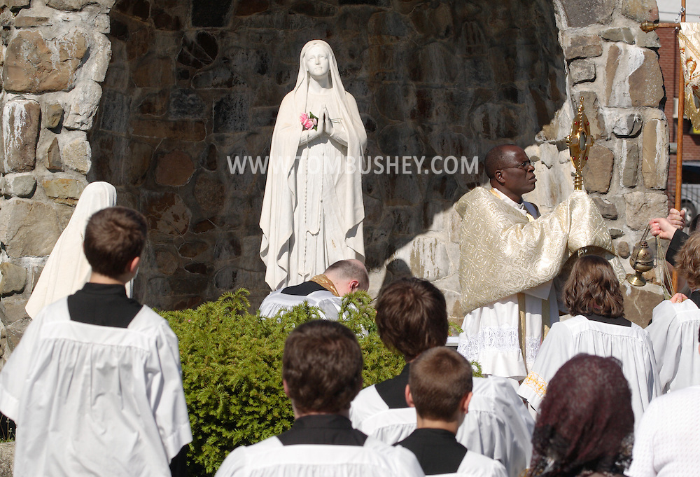 Middletown, NY - A priest from St. Joseph's Church leads a cermony in front of a statue of the Virgin Mary on the feast of Corpus Christi, May 25, 2008.