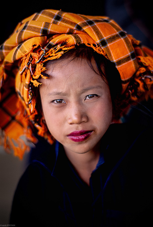 — A young Pao girl rests at the temple on her way from the market to her village.