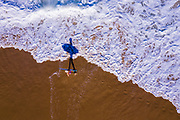 Aerial photo of a woman with a surfboard and a long late afternoon shadow, Shelly Beach, Sunshine Coast, Queensland, Australia