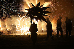 © Licensed to London News Pictures. 06/02/2016.Marsden, UK. ....A man carrying a large metal sun is silhouette by fireworks during the spectacular Imbolc fire festival in Marsden, West Yorkshire, UK. Based on ancient pagan traditions,  Imbolc is a Gaelic festival celebrating the end of winter and the coming of spring. The focal point of the event is the face-off between the Green Man, who represents the coming spring, and Jack Frost, winter - with the former coming out on top. Photo credit : Ian Hinchliffe/LNP