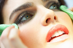 Close up of Woman's Face Wiping Corners of Eyes with Green Gauze