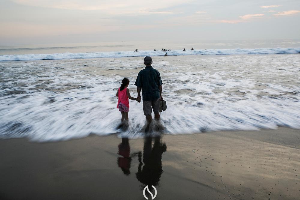 BALI, INDONESIA; APRIL 16, 2015: An elderly man holds his granddaughter's hand on the Batu Belig beach on Thursday, April 16, 2015.