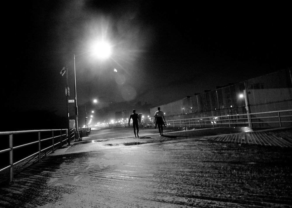 Surfers stroll down the boardwalk after catching the last surf of the day, Rockaway Beach, Queens, NY.