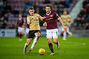 Dean Campbell (#24) of Aberdeen FC runs shoulder to shoulder with Conor Washington (#9) of Heart of Midlothian FC during the Ladbrokes Scottish Premiership match between Heart of Midlothian FC and Aberdeen FC at Tynecastle Stadium, Edinburgh, Scotland on 29 December 2019.