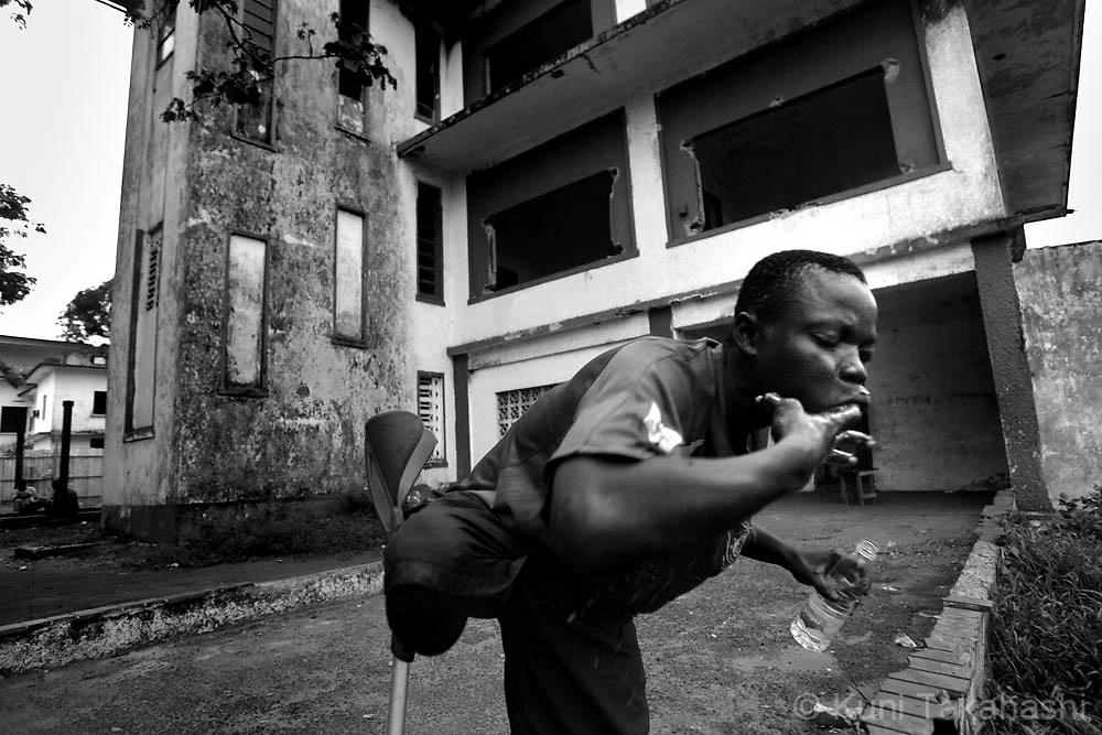 Amputee football player Joseph Kollie, who sleeps in an abandoned building, washes his mouth in Monrovia, Liberia, May 4, 2008. The Liberian National team won the 2008 All Africa Amputee Cup of Nations, but the players - many of them ex-combatants and homeless - continue to struggle, receiving no support from the government or the amputee football league federation.