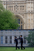 Lunchtime Londoners juxtaposed in front of a construction hoarding beneath the Palace of Westminster, UK's parliament gothic building currently undergoing extensive repairs and renovation.