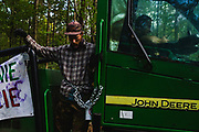 Activist chained himself to the harvester logging machine.