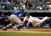 New York Yankees' Rico Noel dives past Toronto Blue Jays catcher Josh Thole to score during a baseball game, Sept. 13, 2015, in New York. <br /> (AP Photo/Kathy Kmonicek)