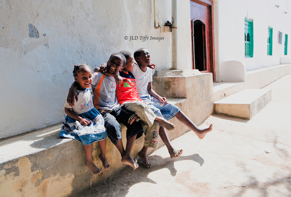 Four laughing children seated together on a bench outside one of the village houses in Mirbat, Oman.  Intense noon sunlight on the whitewashed walls and street.