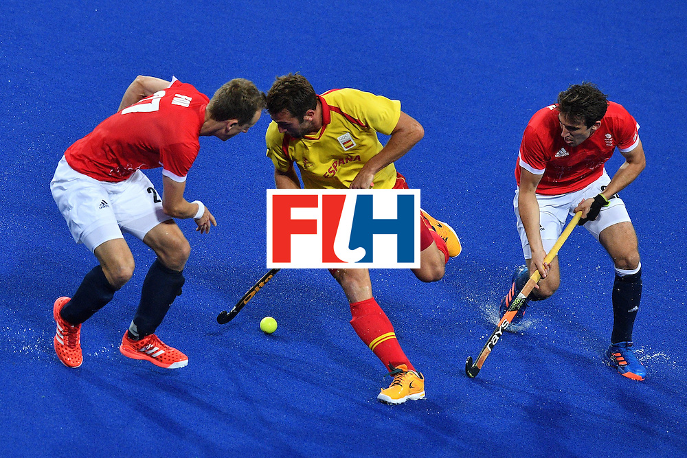 Spain's Xavi Lleonart (C) vies with Britain's Dan Fox (L) and Britain's Iain Lewers during the mens's field hockey Britain vs Spain match of the Rio 2016 Olympics Games at the Olympic Hockey Centre in Rio de Janeiro on August, 12 2016. / AFP / Carl DE SOUZA        (Photo credit should read CARL DE SOUZA/AFP/Getty Images)
