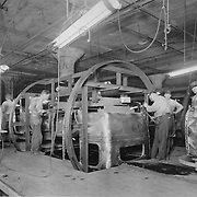 Studebaker workers assemble bodies for 1926 Studebaker automobiles.  The rotisseries allowed workers to spin the bodies 360 degrees.
