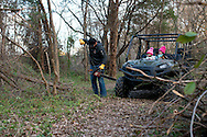 Johny Hendricks starts his chainsaw to cut down brush while his daughters, Adli, 2, and Abri, 4, look on behind his home in Midlothian, Texas on February 27, 2014.