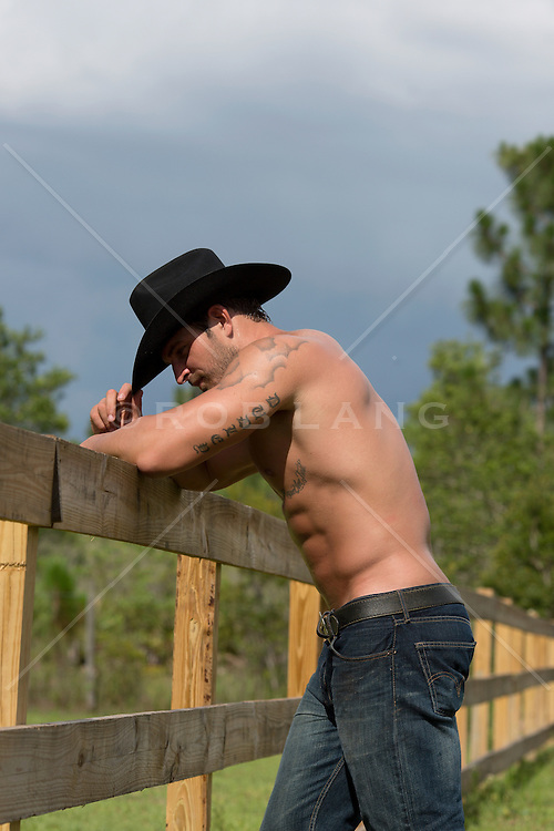 shirtless muscular cowboy on a wooden fence
