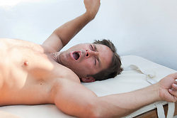 Shirtless man yawning and stretching