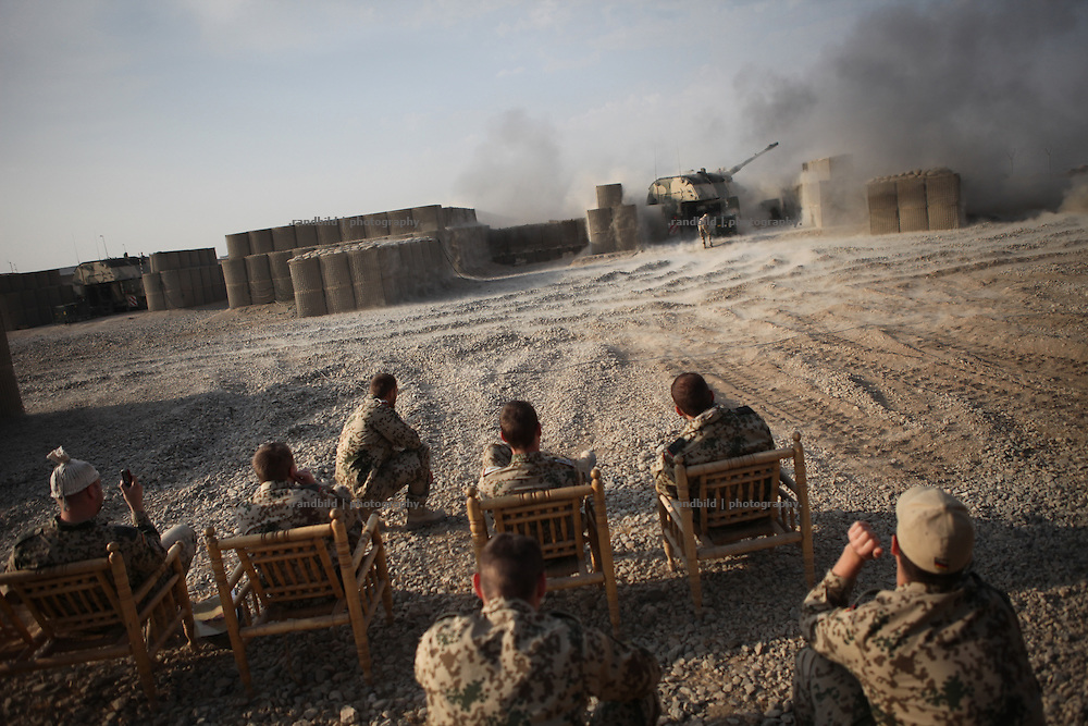 Fellows sit aside and look at an firing Howitzer based in the PRT Kunduz launched for exercise reasons.