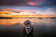 A dramatic summer sunset fills the sky above a white dory at Pine Point in Scarborough, Maine.