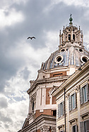 16th century church dome of Santa Maria di Loreto in Rome, beside building with shutters and a bird flying against cloudy gray sky.