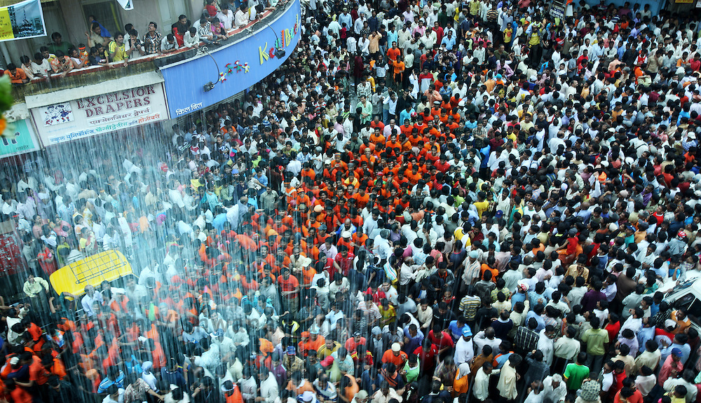 "People pour water on devotees attempting to break a pot containing butter on the occasion of  Krishna Janmashtami (birth of lord Krishna) in Mumbai, September 4, 2007. Janmashtami, which marks the birthday of Hindu god Krishna, will be celebrated across the country on September 4. As legend goes Lord Krishna as a child ate butter kept out of his reach by forming a human pyramid with his friends. Today these ""pots of butter"" contain lakhs of Indian currency as prize money. People form multistoried layers and are ready to risk serious injuries. Photographer: Prashanth Vishwanathan"