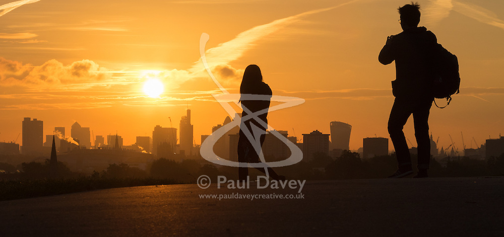 Primrose Hill, London, October 28th 2016. Walkers on Primrose Hill are silhouetted against the city's skyscrapers as dawn breaks over London.