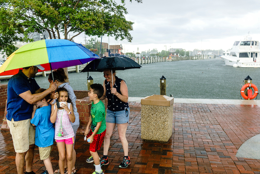 Annapolis, Maryland - June 05, 2016: A thunderstorm prompts two families to huddle under umbrellas at the Kunta Kinte-Alex Haley Memorial park in historic Annapolis Sunday June 5th, 2016. Earlier that day a perigean spring tide brought some of the highest water levels of the year to the coastal town and partially flooded the park. Thunderstorms are a more common cause of nuisance flooding in Annapolis. <br /> <br /> A perigean spring tide brings nuisance flooding to Annapolis, Md. These phenomena -- colloquially know as a &quot;King Tides&quot; -- happen three to four times a year and create the highest tides for coastal areas, except when storms aren't a factor. Annapolis is extremely susceptible to nuisance flooding anyway, but the amount of nuisance flooding has skyrocketed in the last ten years. Scientists point to climate change for this uptick. <br /> <br /> <br /> CREDIT: Matt Roth for The New York Times<br /> Assignment ID: 30191272A