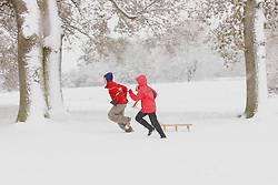 Boy and Girl Running through Snow Pulling Sledge