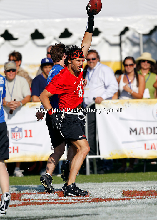 Actor Joe Manganiello (43) of the Famers Gamers team catches a touchdown pass while playing flag football in the EA Sports Madden NFL 11 Launch celebrity and NFL player flag football game held at Malibu Bluffs State Park on July 22, 2010 in Malibu, California. (©Paul Anthony Spinelli)