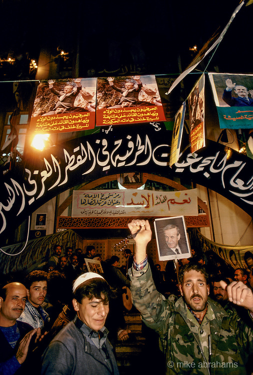 'PERSONALITY CULT OF ASSAD', MEN CHEERING & CELEBRATING BENEATH BANNERS & POSTERS OF ASSAD DURING THE REFERENDUM CAMPAIGN, DAMASCUS, DECEMBER 1991.