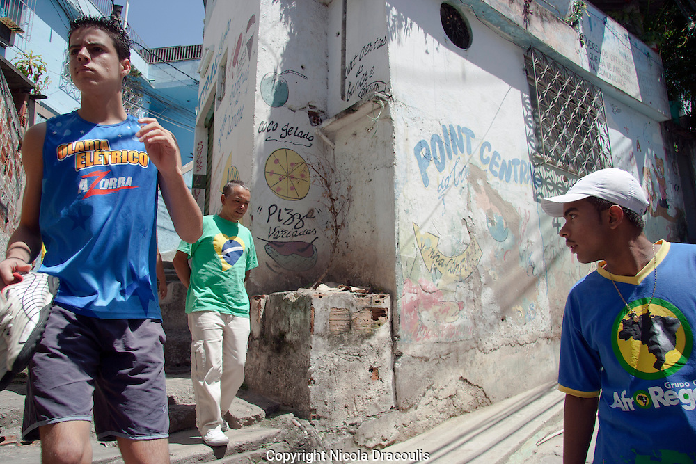 Rafael Teixeira on the streets of Complexo do Alemão, 2006.<br /> Now 25, Rafael is living with his wife and 3 year old son in Complexo do Alemao. Rafael has overcome a lot of challenges in his life. In 2006 he had been struggling to stay out of working for the local drug faction he had just raised enough money to replace the roof to the room that he and his mother are standing in. Unfortunately he succumbed to a crack addiction for 2 years until he was helped by AfroReggae and a local church into rehab. He is now working with AfroReggae in Parada de Lucas on a project interviewing and photographing families in the community. He is proud of where he is today and is mainly focused on providing a good life for his wife and children. <br /> Part of the series Viver no Meio do Barulho (Living in the Middle of the Noise)