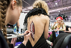 © Licensed to London News Pictures. 25/02/2019. LONDON, UK. A make-up artist applies a Disney-inspired bodypaint to a model at the Warpaint Zone at Professional Beauty, the UK's largest beauty and spa trade show, taking place at Excel London in Docklands.  Photo credit: Stephen Chung/LNP