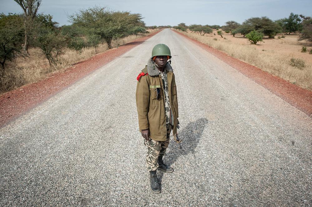 27/01/2013. Route de Sevare Mali. Un militaire malien contrôle la route lors d'une panne de la voiture d'escorte du convoi de journaliste de retour à Sevaré . ©Sylvain Cherkaoui