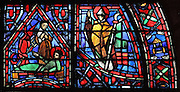 Fulbert on his deathbed with his follower Berenger and a devil representing heresy (left) and the clamor or call to God, a new office against looters and rebels (right), from the Life of Fulbert stained glass window, in the south transept of Chartres Cathedral, Eure-et-Loir, France. This window replaces the original 13th century window depicting the Life of St Blaise, which was destroyed in 1791. It was created in 1954 by Francois Lorin as a gift of the Institute of American Architects, on a theme chosen by the Canon Yves Delaporte. It depicts the life of Fulbert, bishop of Chartres in the 11th century. Chartres cathedral was built 1194-1250 and is a fine example of Gothic architecture. Most of its windows date from 1205-40 although a few earlier 12th century examples are also intact. It was declared a UNESCO World Heritage Site in 1979. Picture by Manuel Cohen