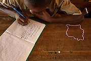 A boy writes in his notebook at the Podio primary school in the village of Podio, Bas-Sassandra region, Cote d'Ivoire on Friday March 2, 2012. The outline of Cote d'Ivoire is drawn with chalk on his desk.