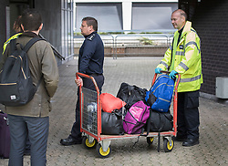 © Licensed to London News Pictures. 18/10/2016. Croydon, UK. Baggage belonging to migrants newly arrived from the Calais jungle camp is unloaded at the Home Office immigration centre in Croydon. British authorities are bringing over about 100 children this week to be reunited with their relatives. The French government have announced that they will be dismantling the camp this month. credit: Peter Macdiarmid/LNP