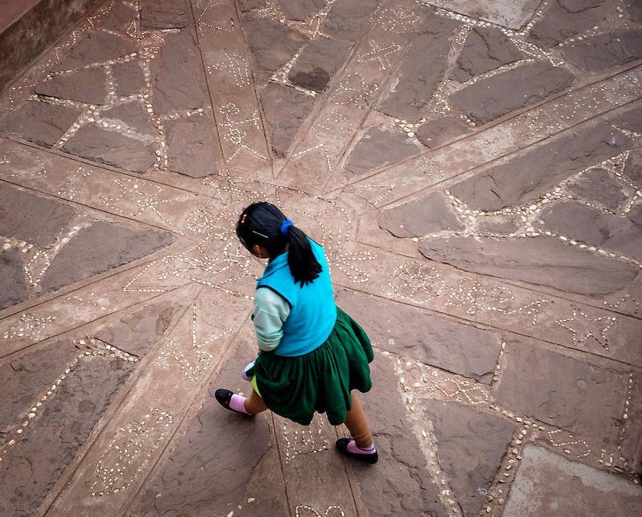 TAQUILE, PERU - CIRCA OCTOBER 2015:  Young woman walking in a typical patio in the Island of Taquile in Lake Titicaca.