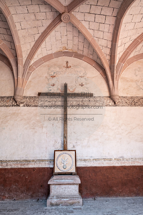 Wooden cross in the courtyard hall at the San Nicolas Tolentino Temple and Ex-Monastery in Actopan, Hidalgo, Mexico. The colonial church and convent  was built in 1546 and combine architectural elements from the romantic, gothic and renaissance periods.