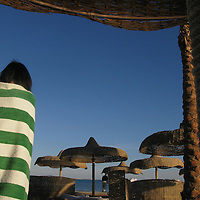 girl in striped towel on a beach with sun shades