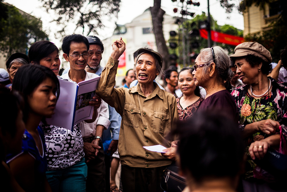 An elder Vietnamese woman speaks to a crowd near Hoan Kiem lake in downtown Hanoi, Vietnam.