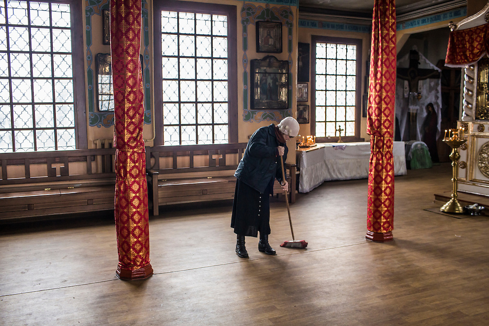 ARTEMIVSK, UKRAINE - FEBRUARY 15: A woman cleans the floor at St. Nicholas Church following the funeral of Igor Molodetskykh, 7, who was killed two days prior when a shell hit his school on February 15, 2015 in Artemivsk, Ukraine. A ceasefire scheduled to go into effect at midnight was reportedly observed along most of the front, save for near the embattled town of Debaltseve. (Photo by Brendan Hoffman/Getty Images) *** Local Caption *** Zhanna Molodetskykh