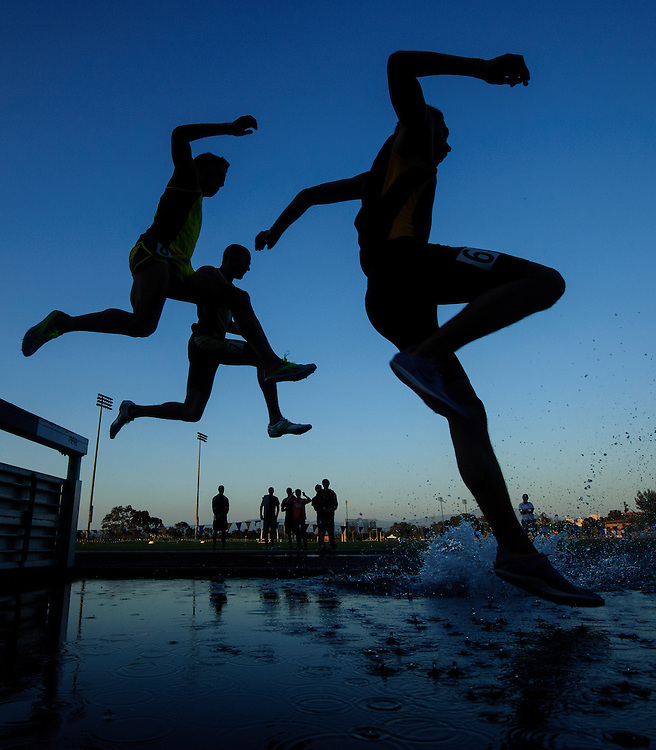 Competitors in the men's 3000m steeplechase leap into the water on the first lap during the Steve Scott Invitational at UC Irvine in Irvine, CA on Saturday, April 28, 2012.