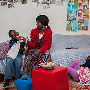 "Atlanta, Georgia/Central Africa Republic Refugee/Nestorine Lakas, 27, feeds her son Eric who has cerebral palsy, while her daughter Carol plays on the floor, at their apartment in Atlanta. Nestorine arrived in the U.S. in 2010 with her two young children from the Central African Republic. Her son, who is now 7 years old, suffers from severe cerebral palsy and requires a wheelchair and specialized healthcare. At the IRC in Atlanta, Nestorine is part of the Temporary Assistance for Needy Families (TANF) program where she is learning English, job skills and basic computer literacy so she can support her family as a single mom and learn how to manage her son's health needs. Unfortunately the father of Nestorine's children was not able to come to the U.S. with her, so she cares for her children and dreams of reuniting with him someday. Nestorine believes what makes her successful is ?working hard and overcoming challenges?. ""There was a war in my country and I fled to Cameroon. I was pregnant with my older son and gave birth along the way. When I fled I was alone. When I got to the camp I found my husbands name on a sign at the camp and we were reunited. My daughter Carol was born in Cameroon."" Because of her son's disability Nestorine got a humanitarian visa with the help of UNHCR. ""I am very happy to be here because they helped me a lot with my child. If I had stayed in CAR there isn't the healthcare that I have here. I am very thankful. The reason my child is still alive because I came as a refugee. Maybe the child would not have had any hope to walk. I hope one day he might walk.""."