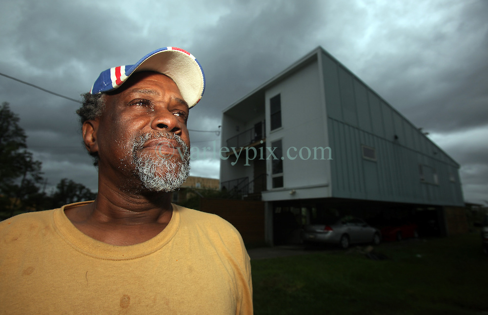 28 August 2012. New Orleans, Louisiana,  USA. <br /> Eye on the storm. Robert Green, survivor of Hurricane Katrina and resident of the Lower 9th Ward sits outside his Brad Pitt inspired 'Make It Right' foundation home watching the first feeder bands of Hurricane Isaac come ashore. He and his family are not evacuating. Mr Green lost his mother and young granddaughter during Hurricane Katrina. Both drowned and he and his surviving family members weathered the storm for 7 hours on the roof of their wrecked house. The 7th year anniversary of Hurricane Katrina is tomorrow and with a storm lurking in the Gulf Mr Green admits to having chills as he remembers the tragedy of 7 years ago.<br /> Photo; Charlie Varley
