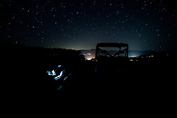 "Cowboy Jim Snyder is illuminated by the light from his ipad as he tries to work a ""star-tracker"" app while stargazing on the ranch. The lights of Snomass Village provide light pollution in the distance."