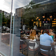 DC's downtown buildings are reflected in the huge glass front windows of Againn, a contemporary gastropub in DC's business district.
