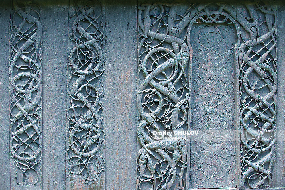 External wooden wall carved decoration of the medieval Urnes Stave church with viking motifs covered with tar in Ornes, Norway.