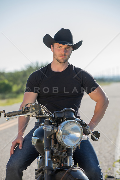 hot cowboy sitting on a motorcycle on a rural road