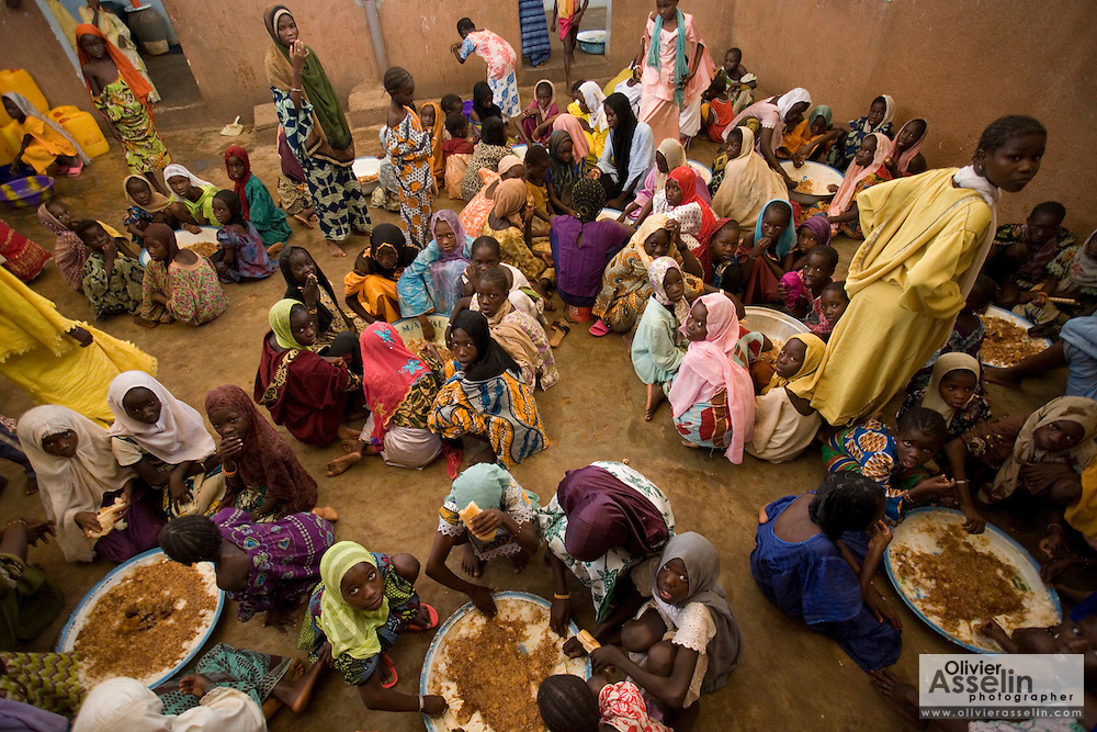 Girls gathered around large plates of food for lunch at the Mame Diarra Bousso koranic school in the village of Porokhane, Senegal, on Monday June 18, 2007.