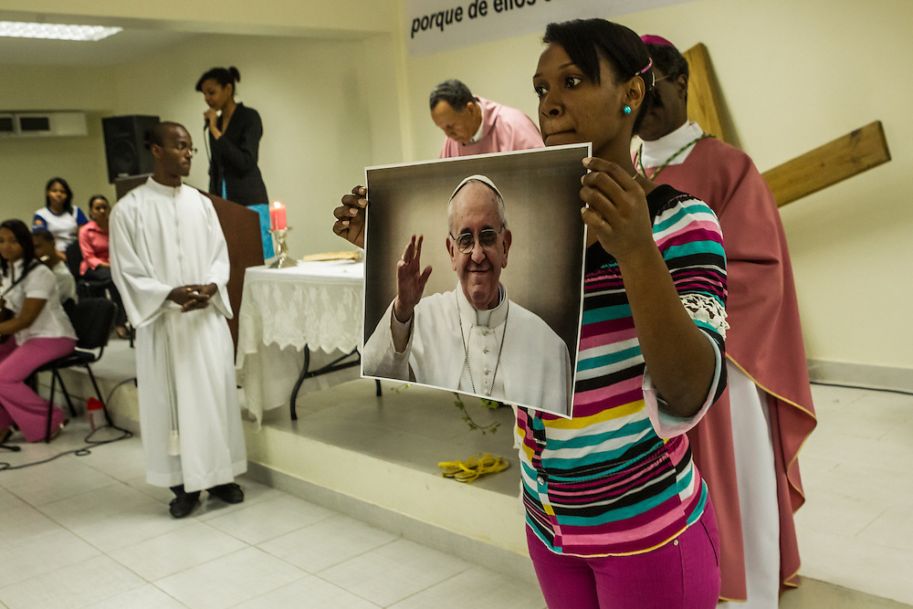"SANTO DOMINGO, DOMINICAN REPUBLIC - MARCH 30, 2014: A teenager holds a photograph of Pope Francis during that she put on the altar during mass given by the new Vatican nuncio to the Dominican Republic, Archbishop Jude Thaddeus Okolo. The teens at this mass represent the Dominican Republic during the Vatican's ""World Youth Day"".   Okolo recently arrived in Santo Domingo to replace the previous Vatican nuncio, Josef Wesolowski, who has been accused by local officials of molesting young boys that work along the malecon here, shining shoes. Several teenagers attending the event told visitors that they had interacted with Wesolowski during local church events, and were suprised by the accusations. CREDIT: Meridith Kohut for The New York Times"